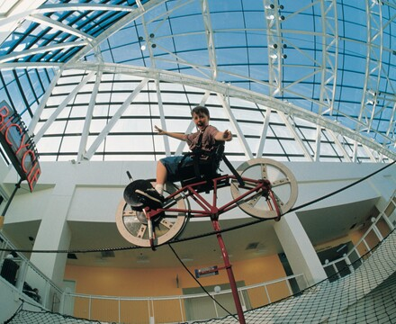 Aided by physics, a boy with outstretched arms balances a bike on a wire.