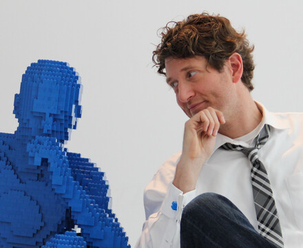 Artist Nathan Sawaya sitting next to Blue Guy Sculpture in The Art of the Brick exhibition