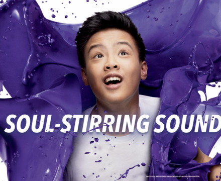 """Image of purple paint splashed around a boy with the words """"soul-stirring sound"""" on the photo"""