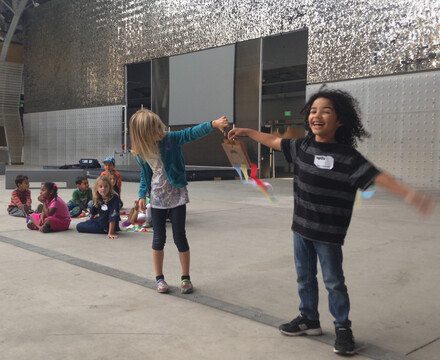 Two happy kids hold hands among friends in a science camp class