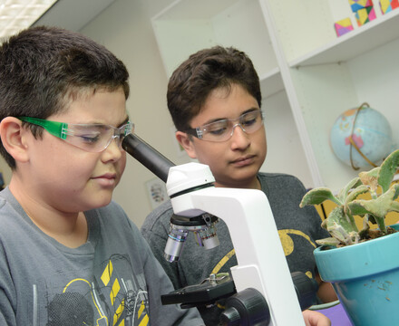 Two youth examine an object through a microscope