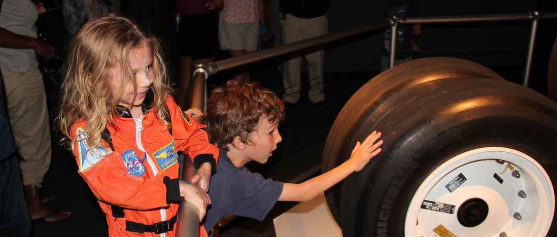 A girl in an astronaut costume with a boy touching space shuttle tires