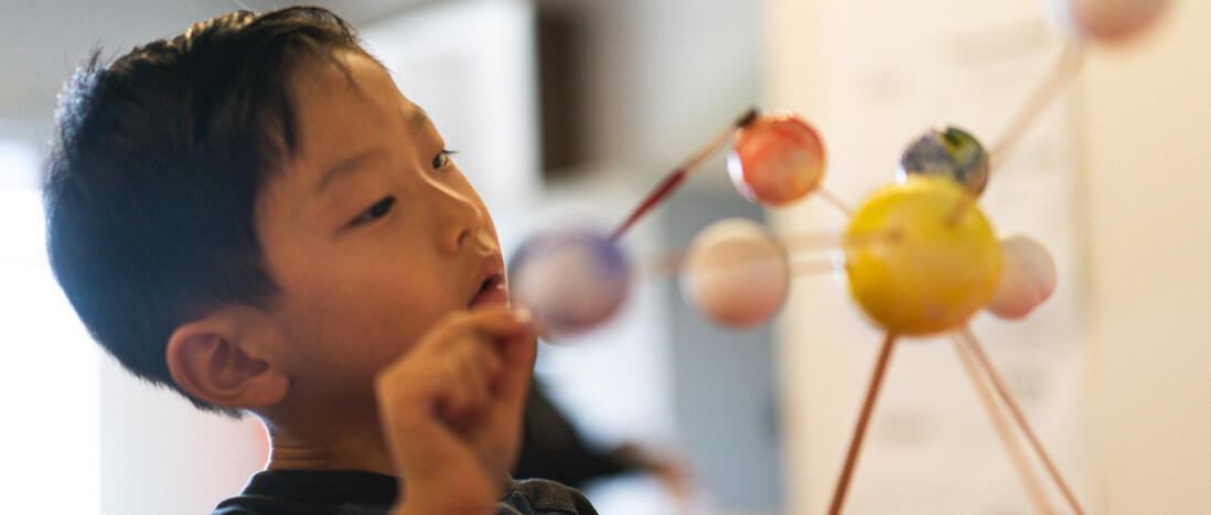 Young boy painting solar system model