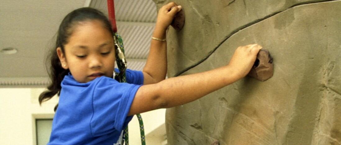 Young girl wearing harness climbs artificial rock wall