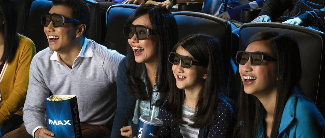 A family wearing 3D glasses and watching a film in the IMAX theater